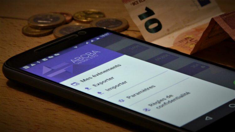 Photo d'un smartphone avec l'application Android Abcba ouverte au milieu de pièces de monnaie et d'un billet.