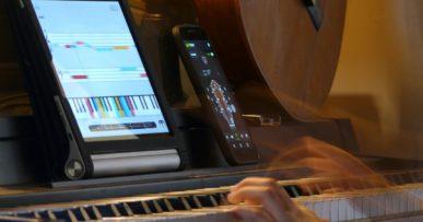 Photo d'une pianiste jouant du piano avec une tablette et un smartphone.