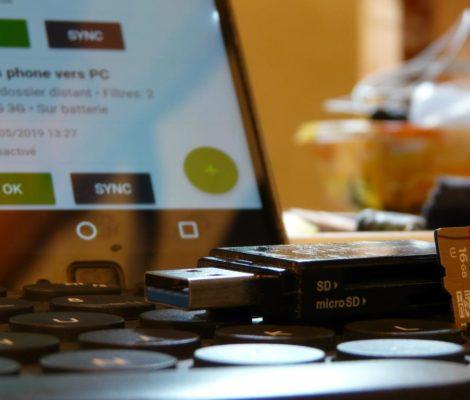 Photo d'un lecteur de cartes mémoires et d'une carte microSD sur un clavier d'ordinateur et application de transfert de fichiers affichée sur smartphone.