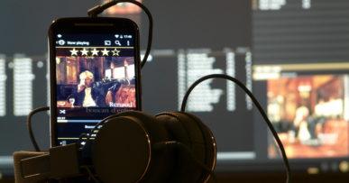 Photo d'un casque audio et d'un smartphone avec l'application MediaMonkey affichée