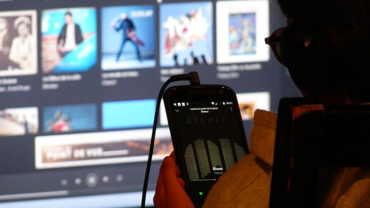 Photo d'une personne écoutant de la musique avec son smartphone avec en fond des jaquettes d'albums sur grand écran