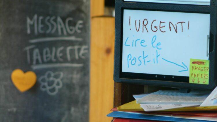 Photo de messages sur un tableau ardoise, une tablette et un post-it indiquant de ranger les papiers d'un meuble classeur.