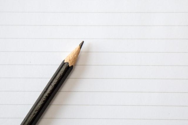 Un crayon de bois posé sur une feuille de papier