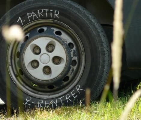 Photo d'une roue avec 1-Partir 2-Rentrer écrits à la craie