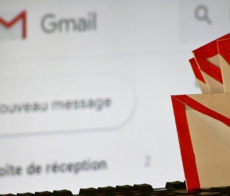 Photo d'envellopes papier aux couleurs de Gmail posées sur un clavier d'ordinateur avec site Gmail en arrière plan.