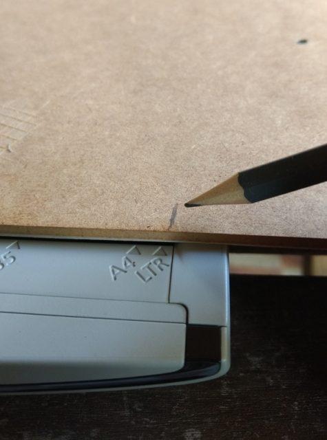 Photo montrant le traçage d'un repère au crayon de bois sur le dos de l'image à numériser.